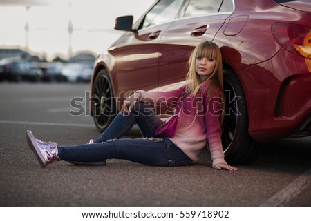 blonde girl sitting near the wheels of the red car