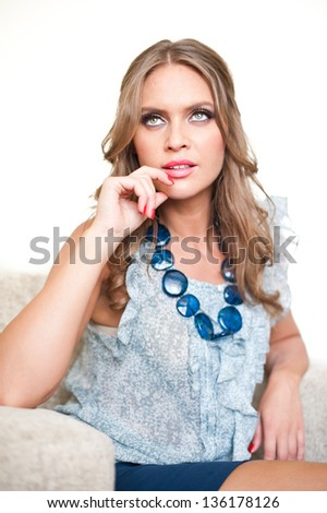 blonde girl sitting on chair and thinking.Woman resting at home looking away, daydreaming, smiling.? Pretty young, blonde woman relaxing on an chair - stock photo