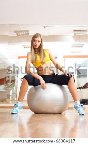 Blonde girl sittinig on silver ball in fitness gym - stock photo
