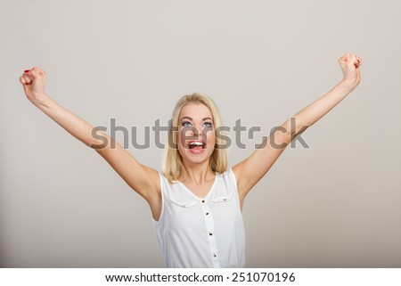 Blonde girl spreading hands with joy, happy successful young woman with arms up. Success positive emotions. - stock photo