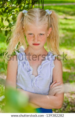Blonde girl standing in the garden with hands clasped, looking out at the forehead and angry - stock photo
