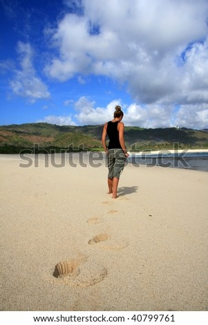 Blonde girl standing on a beach looking out to sea with footprints.