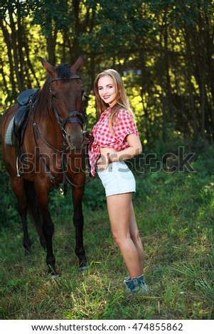 blonde girl walking with a horse in a field