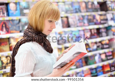 Blonde girl wearing scarf reads book in supermarket; shallow depth of field - stock photo