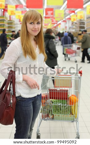 Blonde girl wearing white shirt and cart with food; shallow depth of field - stock photo