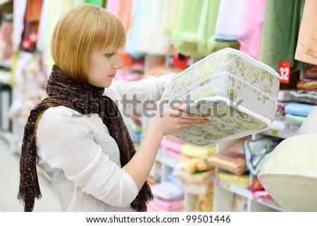 Blonde girl wearing white shirt chooses mattress in shop; shallow depth of field - stock photo