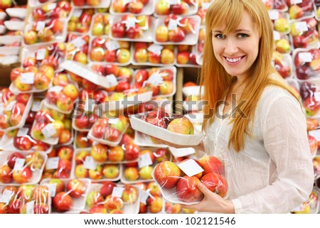 Blonde girl wearing white shirt chooses packed apples in store; shallow depth of field - stock photo