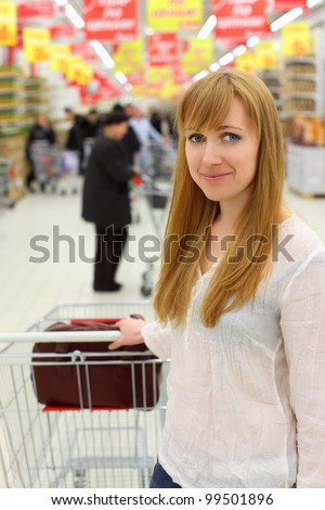 Blonde girl wearing white shirt with empty cart; shallow depth of field - stock photo