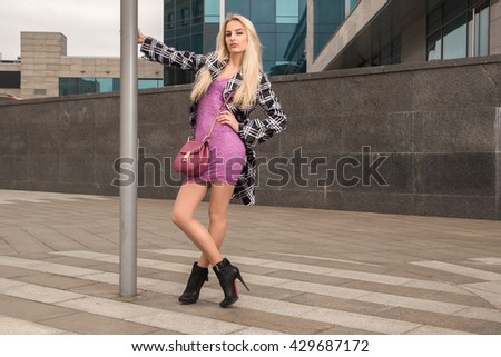 Blonde girl with bag beside the post