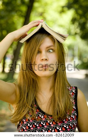 Blonde girl with book over head at the park. - stock photo