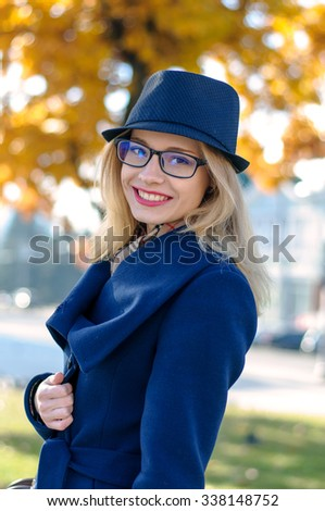 Blonde girl with glasses smiling on a background of yellow foliage