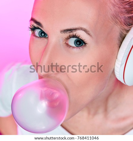 blonde girl with headphones blowing up a bubble of gum on a pink background