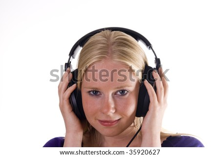 Blonde girl with headphones is listening to music