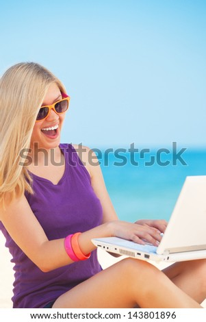 Blonde girl with notebook at the beach. - stock photo