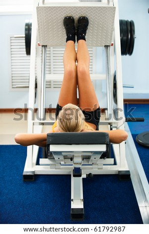 blonde girl working out on leg machine in gym