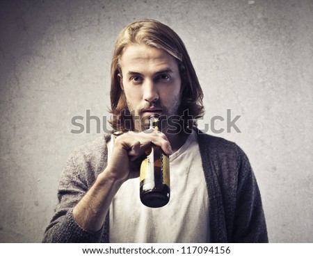 Blonde guy drinking a beer - stock photo