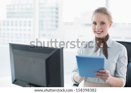Blonde happy businesswoman using tablet in bright office