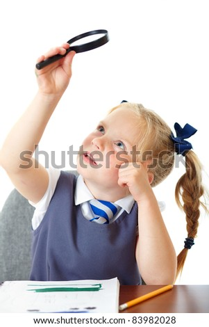 Blonde happy curious schoolgirl in blue dress and matching tie isolated on white holds magnifying glass - stock photo