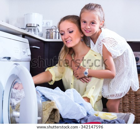 Blonde housewife and little girl doing laundry together - stock photo