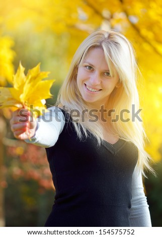 Blonde in a park holding a bouquet of autumn leaves