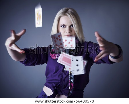 blonde in violet on a grey background scatters playing cards. - stock photo