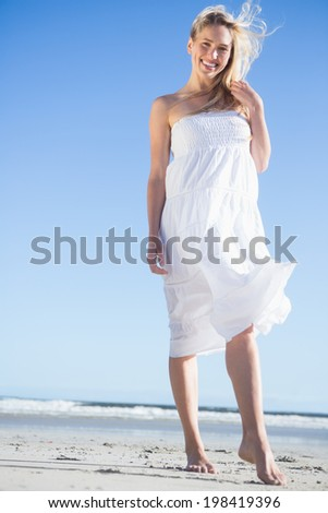 Blonde in white dress smiling at camera on the beach on a bright day