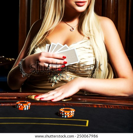 Blonde is playing poker - stock photo