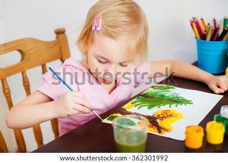 Blonde kid painting with paintbrush - stock photo