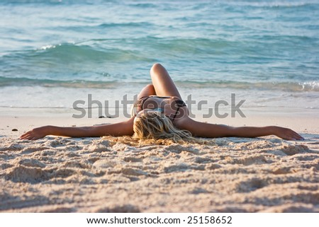 Blonde lady lying on the sand beach