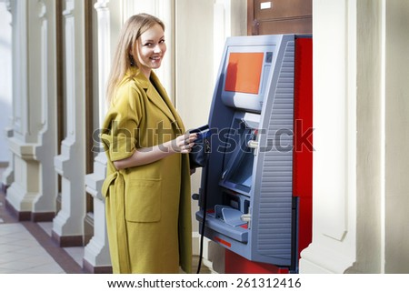 Blonde lady using an automated teller machine . Woman withdrawing money or checking account balance - stock photo