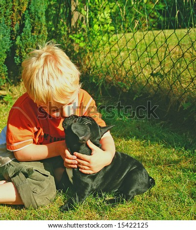 blonde little boy kissing his sweet dog - stock photo
