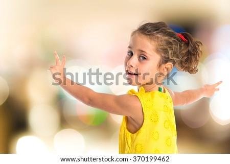 Blonde little girl dancing on unfocused background - stock photo