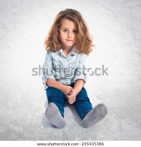 Blonde little girl on the floor - stock photo