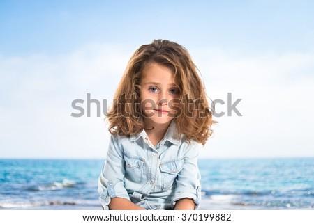 Blonde little girl on unfocused background - stock photo