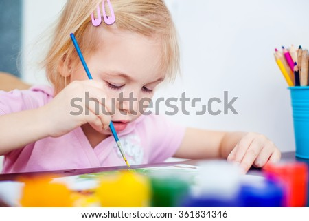 Blonde little girl painting with paintbrush  - stock photo