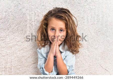 Blonde little girl pleading over textured background   - stock photo