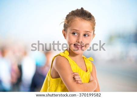 Blonde little girl walking with her arms crossed on unfocused background - stock photo
