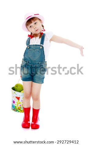 Blonde little girl with a short pigtail with a pink hat , overalls and boots holding a striped ball with which she played at the cottage - stock photo