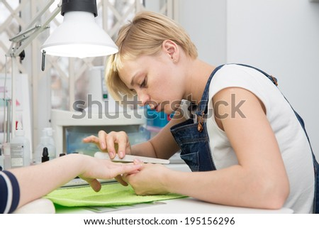 blonde manicurist  sawing client nails - stock photo