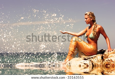 Blonde mermaid sitting on the rocky beach