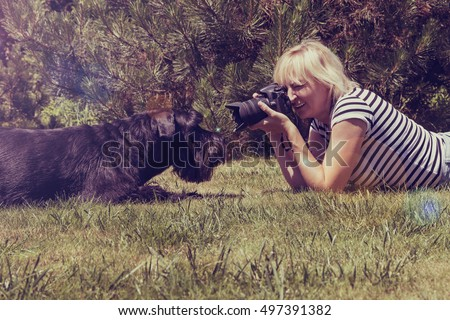 Blonde middle aged woman is lying on the lawn against her lying Giant Black Schnauzer dog and is taking picture. Photo is edited like vintage photo with lens flare effect.