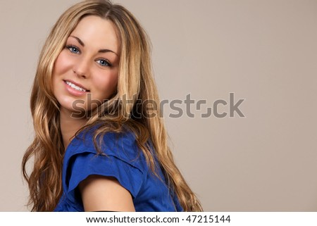 Blonde Model In A Blue Top Against A Neutral Background