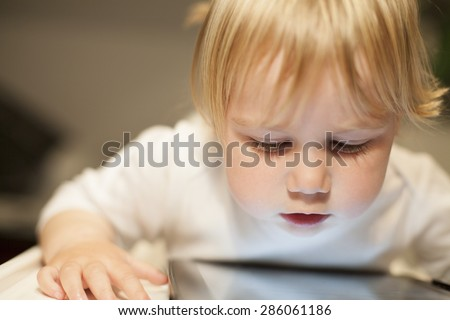 blonde nineteen month age baby white sweater looking at close digital tablet inside home - stock photo