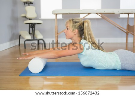Blonde patient lying on floor doing exercise in bright room