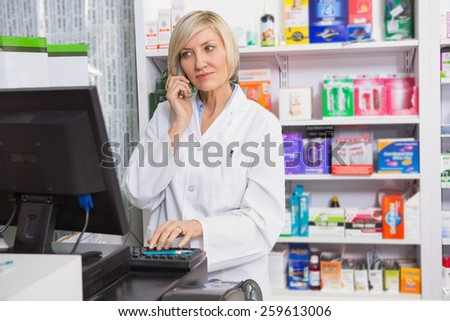 Blonde pharmacist using computer while phoning in the pharmacy - stock photo