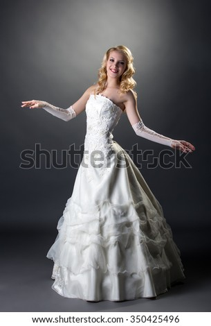 Blonde posing in wedding dress with embroidery - stock photo