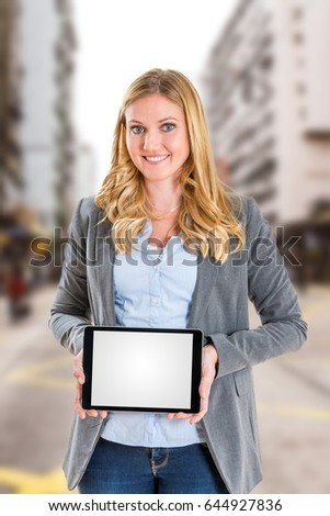 Blonde real estate broker holding blank tablet screen into camera in urban environment