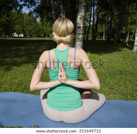blonde real girl doing yoga in green park on grass - stock photo