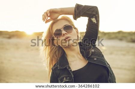 Blonde rocker girl on beach wearing aviator sunglasses and ripped demin jacket - stock photo