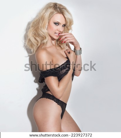 Blonde sexy woman posing over white background in black lingerie, looking at camera. - stock photo